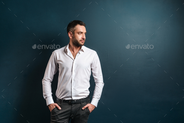 Handsome serious man standing over dark blue background - Stock Photo - Images