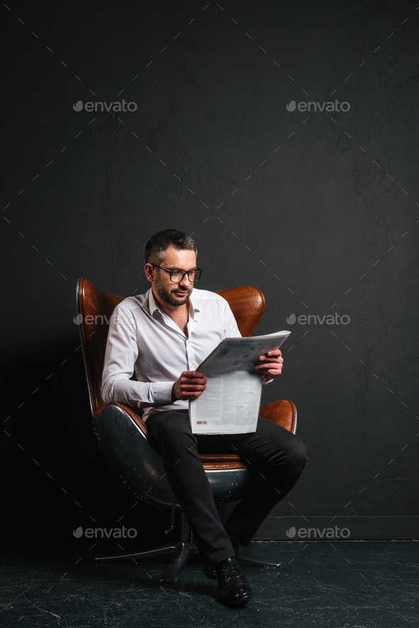 Handsome businessman reading newspaper. - Stock Photo - Images