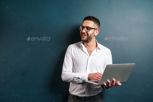 Happy man wearing glasses using laptop computer. - Stock Photo - Images