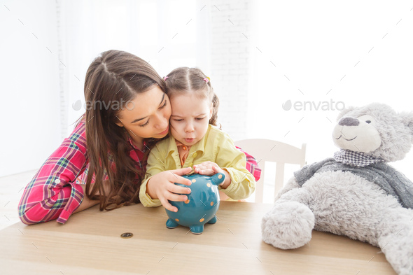 Mother and her child daughter putting coin to piggy bank - Stock Photo - Images