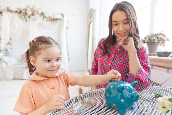 Mom teaches a little daughter to collect money in a piggy bank - Stock Photo - Images