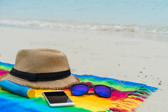 Hat and sunglasses with mobile phone on colorful colth on white sand beach - Stock Photo - Images