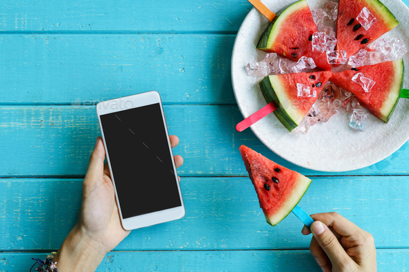 Watermelon slice popsicles with colorful stick and hand holding smart phone - Stock Photo - Images