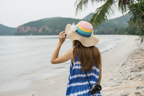 Young woman with camera relaxing and enjoying at the tropical beach - Stock Photo - Images