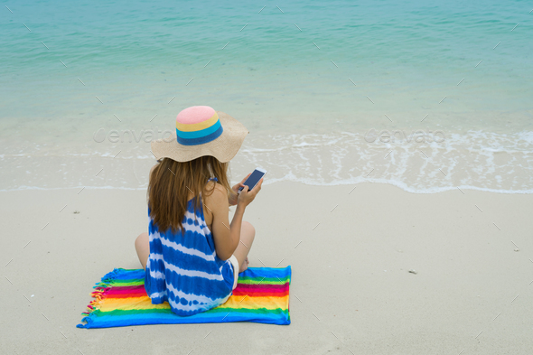 Young woman relaxing and using mobile phone at the tropical beach - Stock Photo - Images