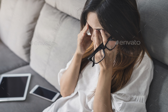 Young woman take off her glasses and siiting on sofa - Stock Photo - Images