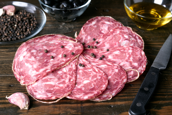 slices of Iberian sausage on wooden board - Stock Photo - Images