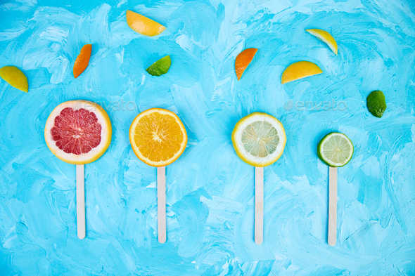 Citrus slice popsicles on a blue background. - Stock Photo - Images