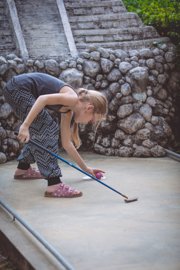 Happy little girl  playing mini golf. - Stock Photo - Images