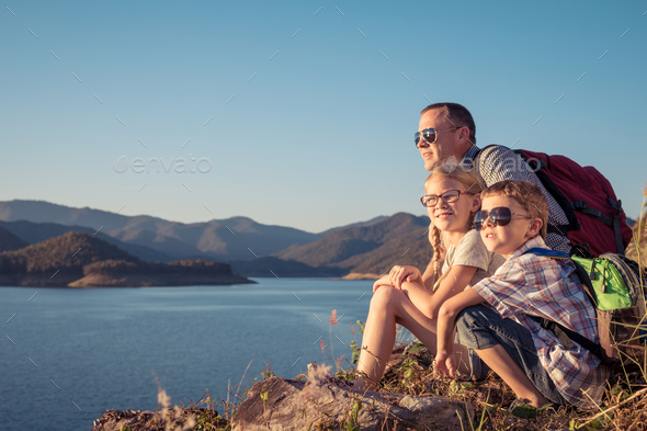 Happy family sitting near a lake at the day time. - Stock Photo - Images