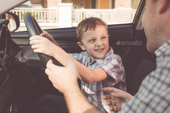 Happy father and son sitting in the car at the day time. - Stock Photo - Images