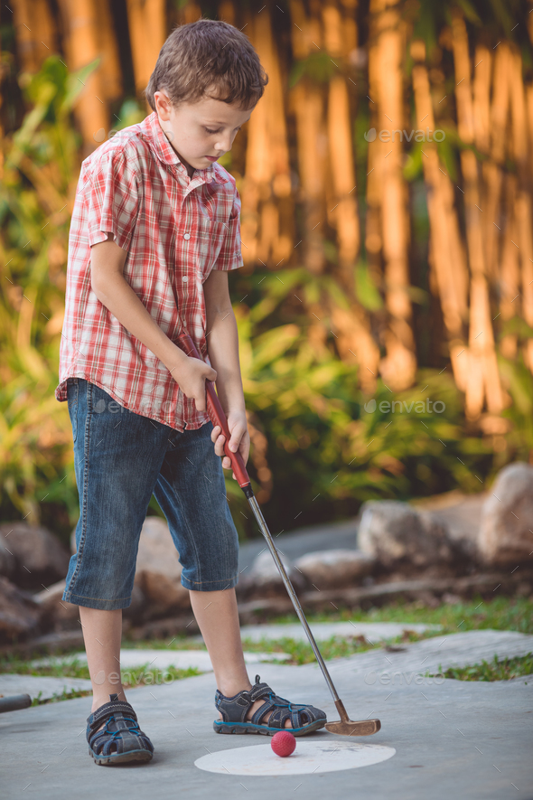 Happy little boy  playing mini golf. - Stock Photo - Images
