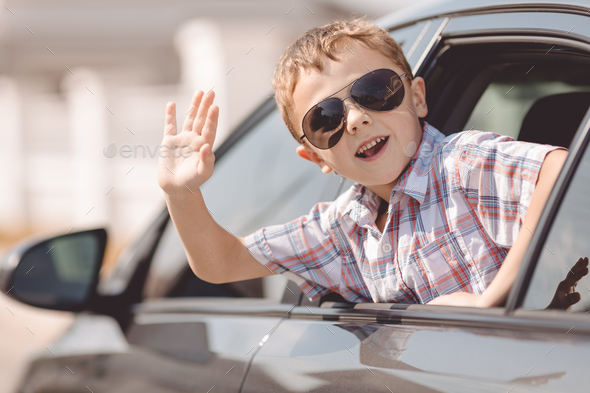 One happy little boy sitting in the car. - Stock Photo - Images