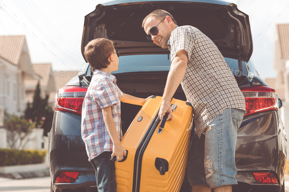Happy father and son getting ready for road trip on a sunny day. - Stock Photo - Images