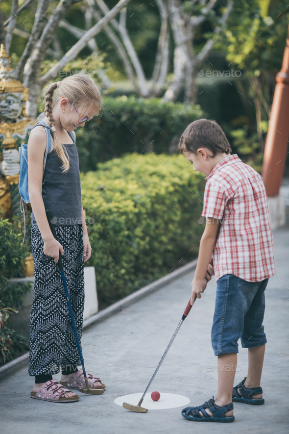 Happy brother and sister  playing mini golf. - Stock Photo - Images