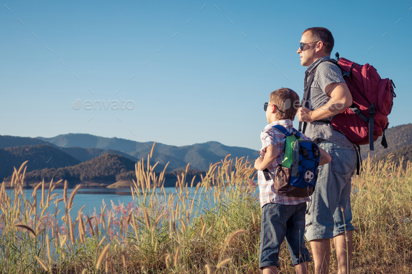 Happy family standing near the lake at the day time. - Stock Photo - Images