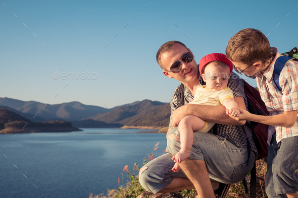 Happy family sitting near the lake at the day time. - Stock Photo - Images