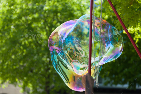 Arstist blowing colorful giant soap bubbles outdoor - Stock Photo - Images
