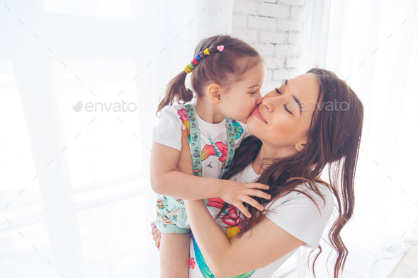 Little girl kissing her young mother - Stock Photo - Images