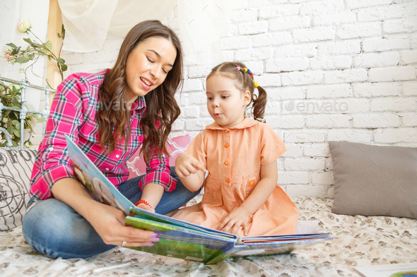 Young mother and her child girl reading a book - Stock Photo - Images