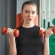 Sporty Young Woman Exercising with Dumbbells in the Gym - VideoHive Item for Sale