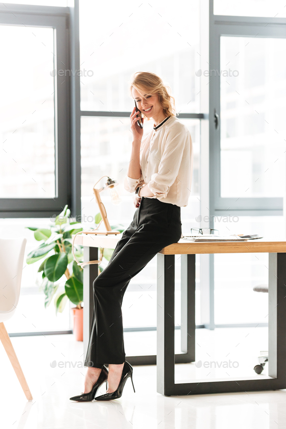 Portrait of a smiling young businesswoman talking - Stock Photo - Images