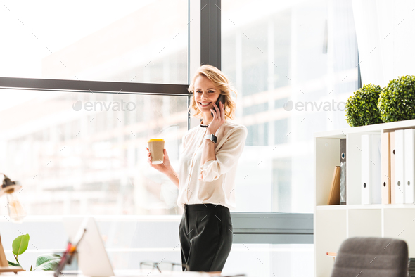 Amazing young business woman in office talking by mobile phone drinking coffee. - Stock Photo - Images