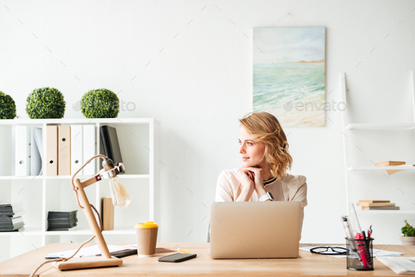 Beautiful young business woman sitting in office - Stock Photo - Images
