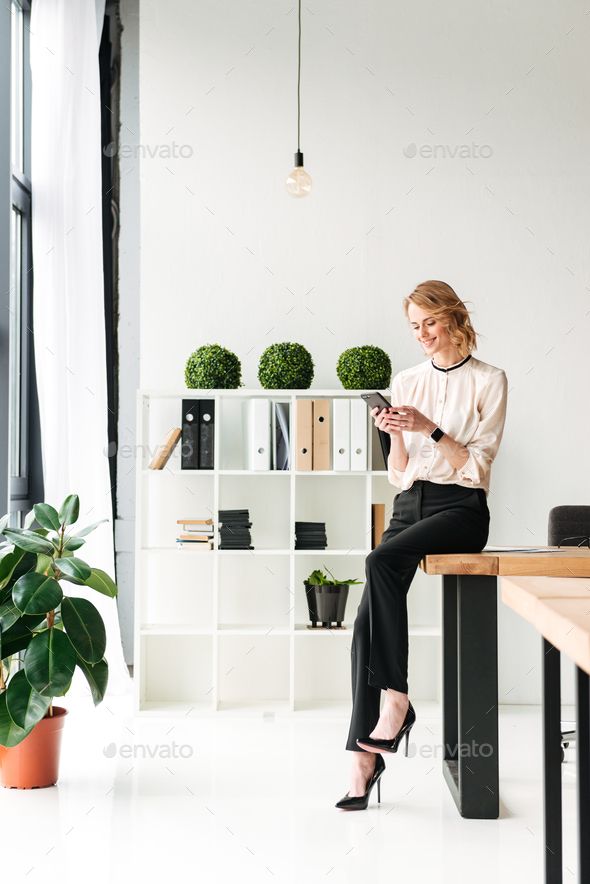 Happy young business woman in office chatting by mobile phone. - Stock Photo - Images