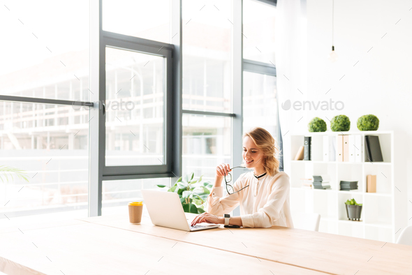 Happy young business woman sitting in office using laptop - Stock Photo - Images