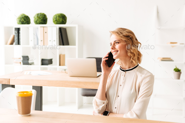 Pretty young business woman talking by mobile phone. - Stock Photo - Images