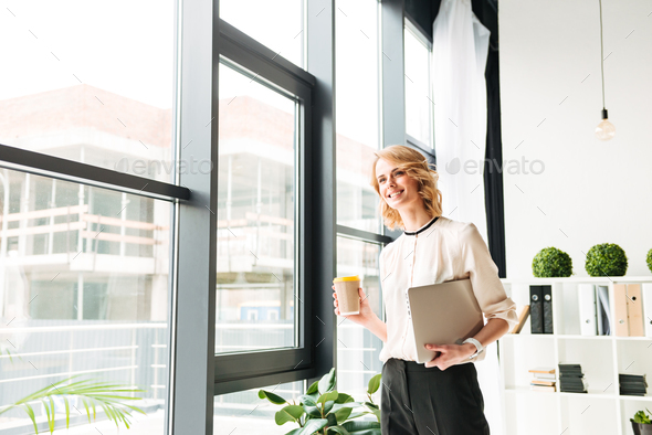Cheerful young business woman holding laptop computer looking aside drinking coffee. - Stock Photo - Images