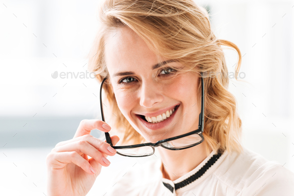 Cheerful young business woman in office - Stock Photo - Images