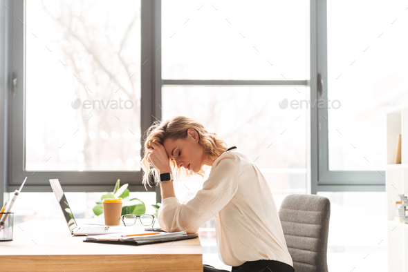 Tired young business woman sitting in office using laptop - Stock Photo - Images