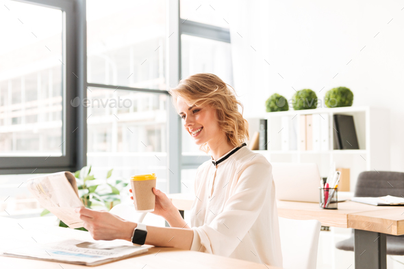 Smiling young business woman reading newspaper drinking coffee. - Stock Photo - Images