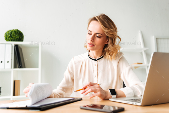 Serious young business woman sitting in office - Stock Photo - Images