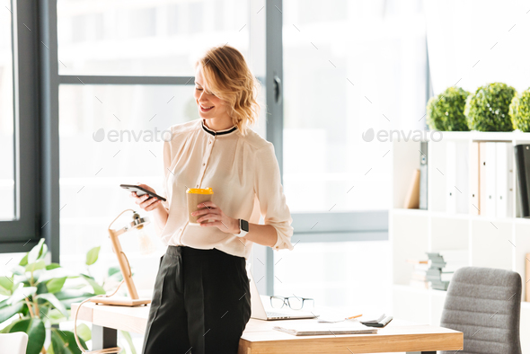 Amazing young business woman chatting by mobile phone drinking coffee. - Stock Photo - Images