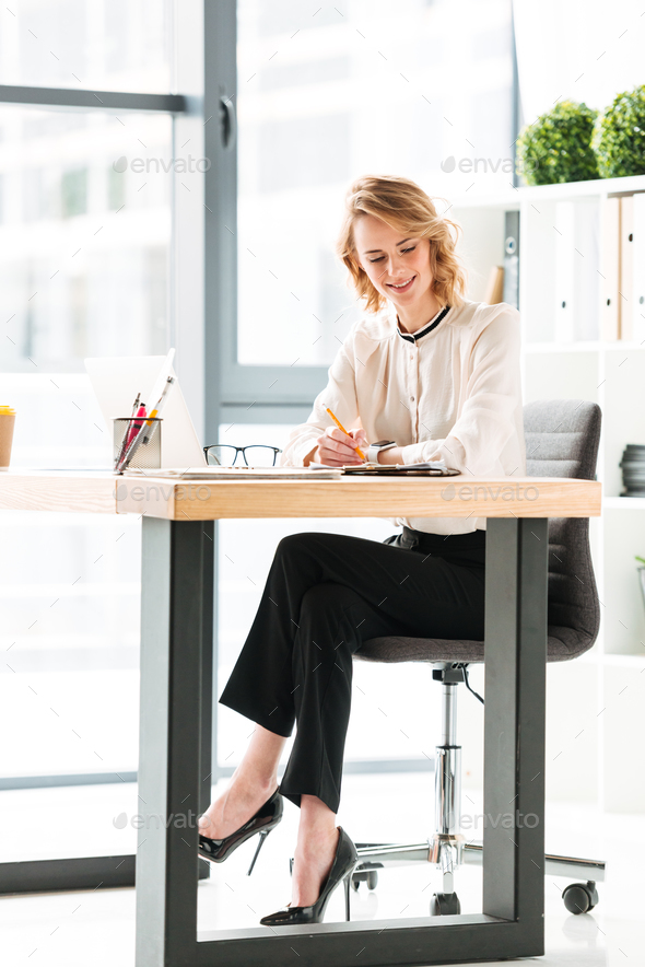 Portrait of a smiling young businesswoman working - Stock Photo - Images