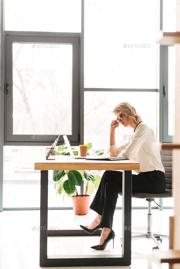 Serious young business woman using laptop computer looking aside. - Stock Photo - Images
