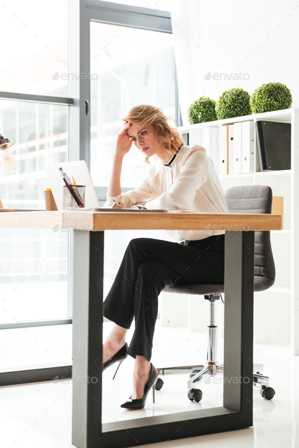 Portrait of a serious young businesswoman working - Stock Photo - Images