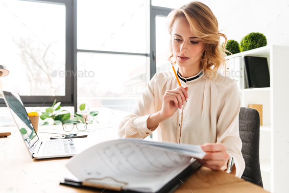 Portrait of a beautiful young businesswoman working - Stock Photo - Images