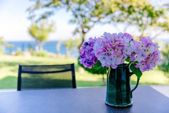 bouquet of pink and purple flowers in a vase on the table in the garden - Stock Photo - Images