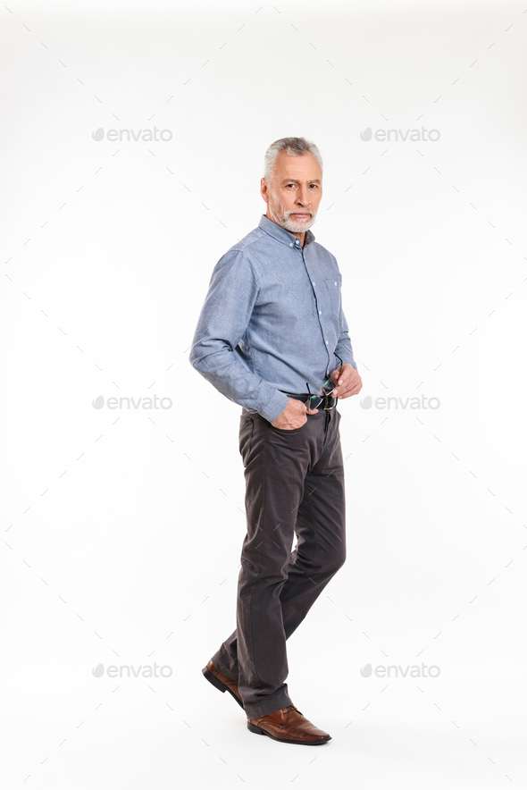 Full-length shot of old man looking camera seriously isolated - Stock Photo - Images