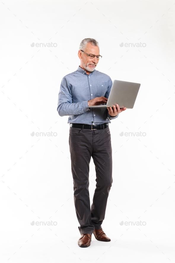 Cheerful mature man in eyeglasses using laptop computer - Stock Photo - Images
