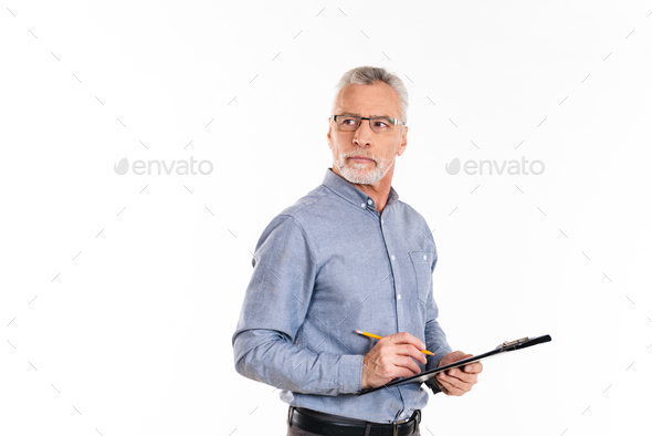 Serious confident man in glasses holding folder and looking away - Stock Photo - Images