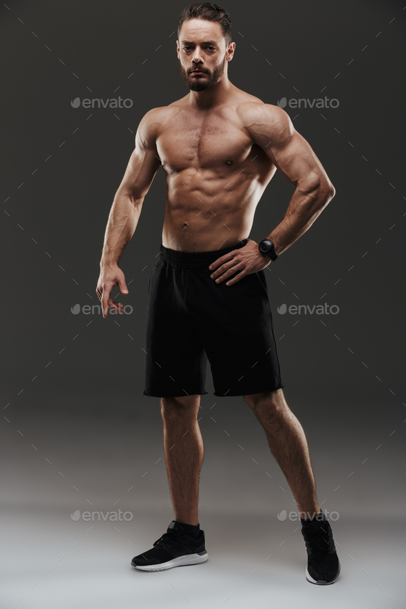 Full length portrait of a serious muscular man posing - Stock Photo - Images