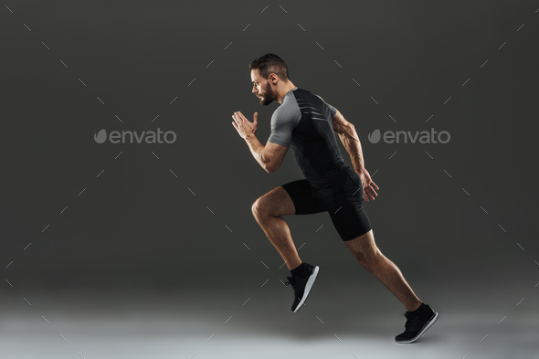 Side view of a concentrated muscular sportsman - Stock Photo - Images