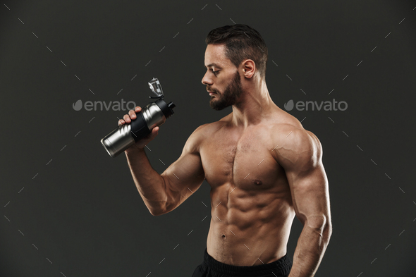 Portrait of a strong muscular bodybuilder drinking water - Stock Photo - Images
