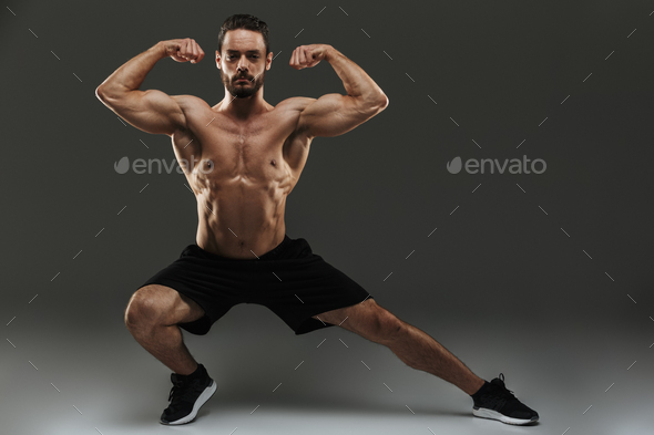 Portrait of a fit muscular bodybuilder flexing biceps - Stock Photo - Images