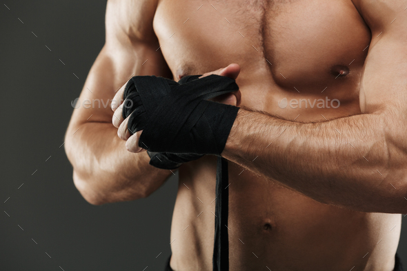 Close up of a muscular man tying boxing bandages - Stock Photo - Images